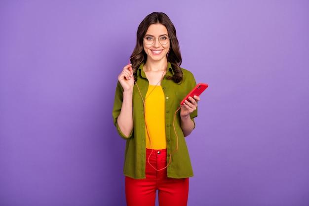 ポジティブで陽気な女の子の肖像画は、夏の自由時間を楽しむスマートフォンを使用する音楽ヘッドセットを着用する紫の色の背景に分離されたパンツ