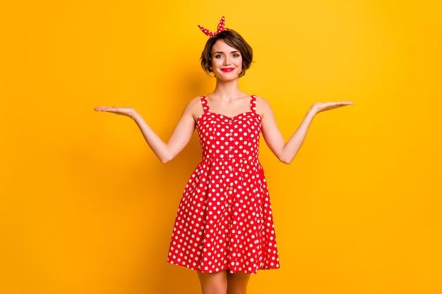 Портрет позитивной жизнерадостной девушки, держащей руку, показ рекламы, продвижение, рекомендую, предлагаю выбрать объект предложения, носить красную юбку в горошек, изолированную над блестящей цветной стеной