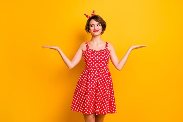 Портрет позитивной жизнерадостной девушки, держащей руку, выглядишь, показывай рекламу, выбирай, решай, надеть красный наряд в горошек, винтаж, изолирован на стене желтого цвета