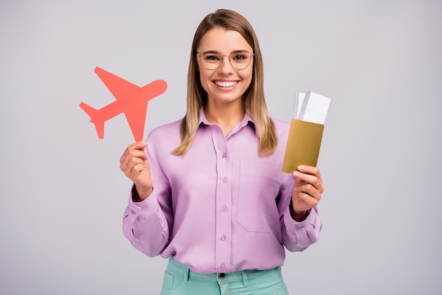 Портрет позитивной веселой девушки с бумажной карточкой, самолет готов к поездке за границу, покупка трансфера на визу, первоклассная одежда, красивая одежда, изолированная на сером цветном фоне