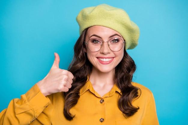 Портрет позитивной жизнерадостной девушки-промоутера соглашается, что рекламный ролик показывает символ большого пальца в желтой красивой одежде, изолированной на синем цветном фоне