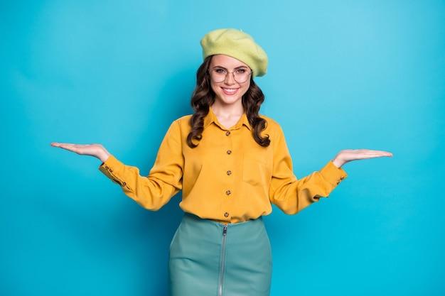 Портрет позитивной веселой девушки, промоутер, держится за руку, показывает сравнение рекламы, вариант измерения, носить желтую блузку, изолированную на синем цветном фоне