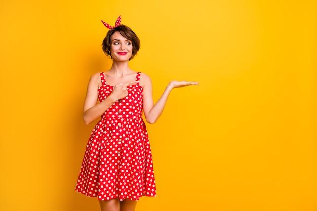 긍정적 인 명랑 소녀 발기인의 초상화 손 모양 옵션 광고 프로모션 포인트 검지 손가락 착용 폴카 도트 복고풍 손질 빨간 치마 밝은 색상 벽 위에 절연