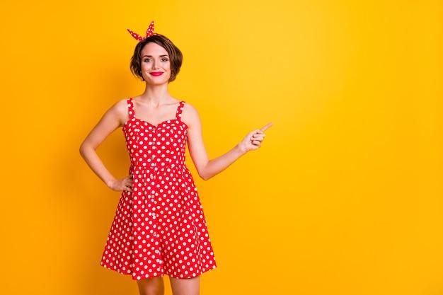 Портрет позитивной жизнерадостной девушки-промоутера указывает указательным пальцем на copyspace демонстрирует рекламную одежду, летнюю одежду в стиле ретро, изолированную над яркой цветной стеной