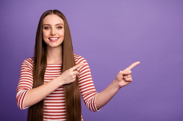 긍정적 인 명랑 소녀 발기인 포인트 검지 손가락 copyspace의 초상화는 광고 홍보가 바이올렛 컬러 벽 위에 고립 된 선택 착용 점퍼를 제안하는 것을 나타냅니다.