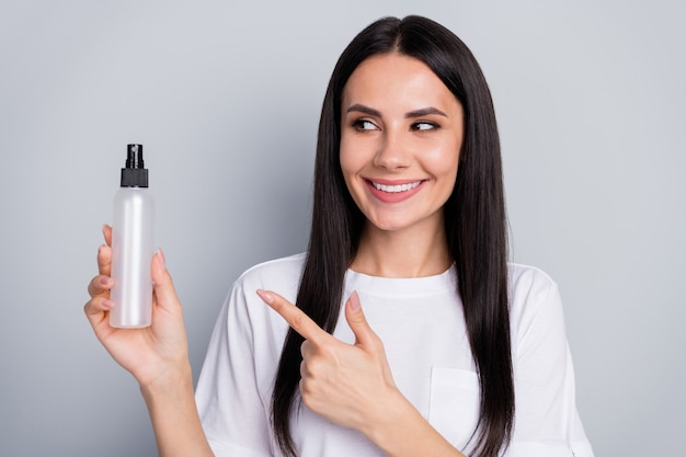 ポジティブな陽気な女の子のプロモーターの肖像画は、新しい衛生ディスペンサーを試してみてください灰色の背景の上に分離されたポイントインデックス指着用白いtシャツを示しています