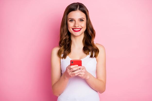 긍정적 인 명랑 소녀의 초상화 사용 핸드폰 이빨 미소
