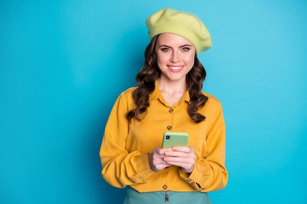스마트폰을 사용하는 긍정적인 쾌활한 소녀의 초상화는 게시물 댓글 공유 소셜 미디어 뉴스 착용을 즐깁니다. 파란색 배경에 격리된 멋진 모자