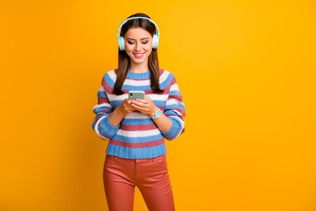 헤드폰에 긍정적 인 명랑 소녀 사용 스마트 폰의 초상화는 음악을들을