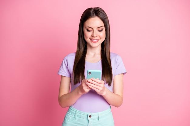 Портрет позитивной жизнерадостной девушки, использующей смартфон, читать, делиться репостом, подписываться на новости социальных сетей, носить фиолетовые бирюзовые брюки, брюки, брюки, изолированные на розовом цветном фоне