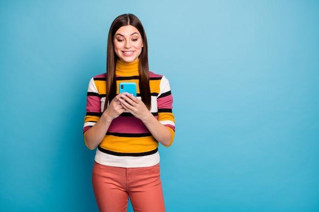 ポジティブで陽気な女の子の肖像画はスマートフォンを使用しますソーシャルネットワーク情報を読みますコメントを共有しますフィードバックは青い色の壁に隔離されたスタイリッシュな赤いジャンパーを着用します