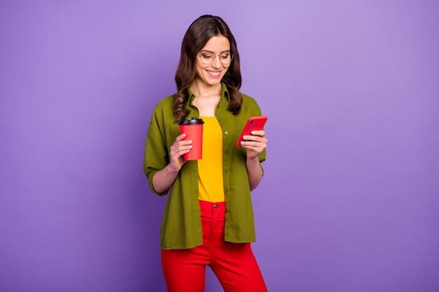 ポジティブな陽気な女の子の肖像画は、スマートフォンのテキストメッセージタイピングチャットチリングホールドテイクアウェイラテカップウェアスタイルスタイリッシュなトレンディな赤いズボン紫の色の背景に分離