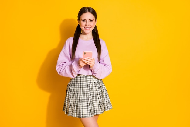ポジティブで陽気な女の子の肖像画はスマートフォンを使用します