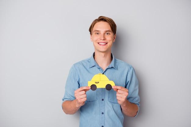 ポジティブで陽気な男の肖像画は黄色の紙カードを保持しますタクシー車は灰色の背景の上に分離された格好良い服を着て快適で簡単な乗り心地をお勧めします