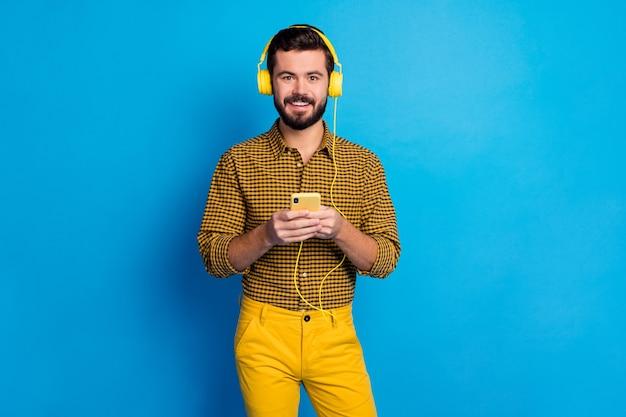 긍정적 인 쾌활한 남자의 초상화는 그가 휴대 전화에서 인터넷을 검색하는 음악 라디오 노래를 듣고 총 노란색 헤드셋 체크 무늬 바지는 파란색 위에 절연 빛나