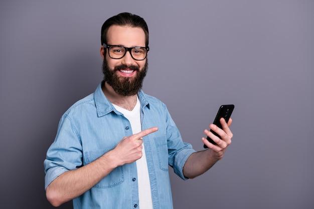 긍정적 인 쾌활한 남자 현대 기술 상점 노동자의 초상화 현재 새로운 스마트 폰 참신 포인트 검지 손가락은 회색 벽 위에 고립 된 멋진 옷을 입는다.