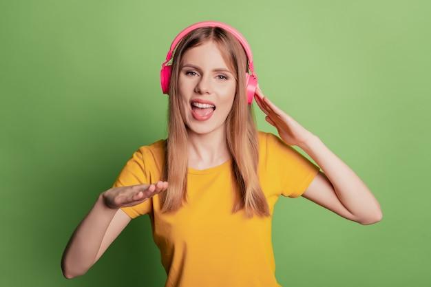 긍정적인 쾌활한 힙스터 dj 레이디의 초상화는 녹색 배경에 노란색 티셔츠를 입고 음악을 듣습니다.