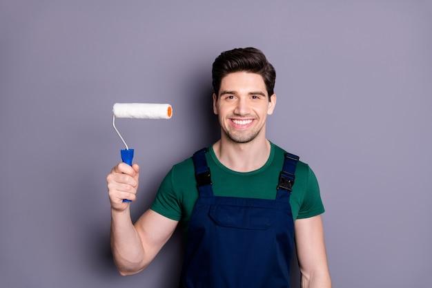 Портрет позитивного веселого маляра держит белый ролик, готовый сменить дом, носить зеленую футболку синюю униформу, изолированную над серой стеной