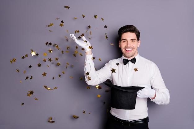 Портрет позитивного жизнерадостного иллюзиониста, держащего цилиндрическую шляпу, заставляет фокус заклинания золотая звезда конфетти летать в воздухе носить белую рубашку черный лук, изолированный на серой стене