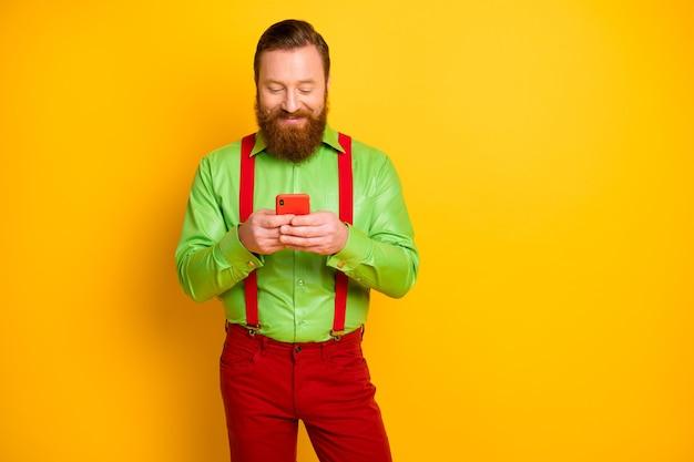 ポジティブで陽気なアイルランド人の肖像画は携帯電話を使用しますブログをフォローしますコメントを投稿しますフィードバックウェアサスペンダーズボンは輝きの色の上に分離されています