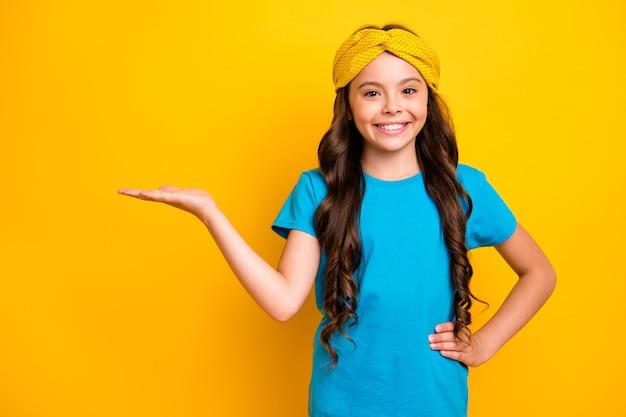 Портрет позитивного жизнерадостного малыша, промоутер, держась за руку, показывать рекламу