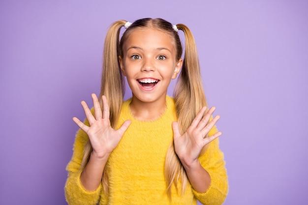 긍정적 인 쾌활한 아이의 초상화는 그녀의 생일 새해 선물 비명 와우 omg 손을 들어 보라색 컬러 벽 위에 절연 노란색 풀오버를 착용에 대한 멋진 뉴스를 듣고