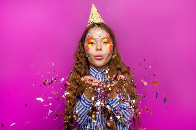 ポジティブで陽気な少女の肖像画は、紫色の壁の曲がりくねった飛行の上に分離された楽しみを持っています