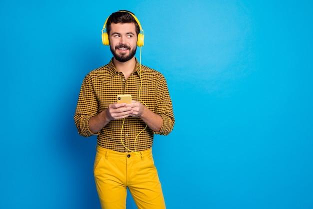 긍정적 인 쾌활한 남자의 초상화 여가 시간을 즐길 음악 멜로디 사용 스마트 폰 착용 헤드셋 밝은 격자 무늬 바지는 파란색 위에 절연