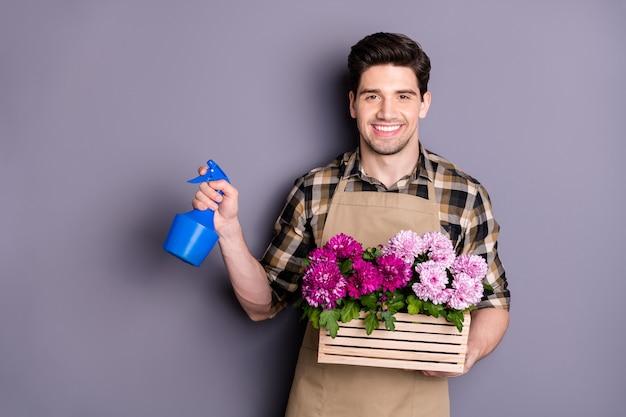 식물 꽃 스프레이 분무기에 대한 자신의 작은 정원 관리를 갖는 긍정적 인 쾌활한 남자 플로리스트 작업자의 초상화 회색 벽 위에 절연 체크 무늬 격자 무늬 셔츠를 착용