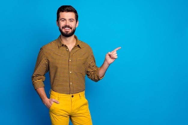긍정적 인 쾌활한 남자 발기인 포인트 검지 손가락 copyspace의 초상화는 광고 승진이 파란색 위에 고립 된 세련된 체크 무늬 의류를 선택 착용 제안을 나타냅니다.