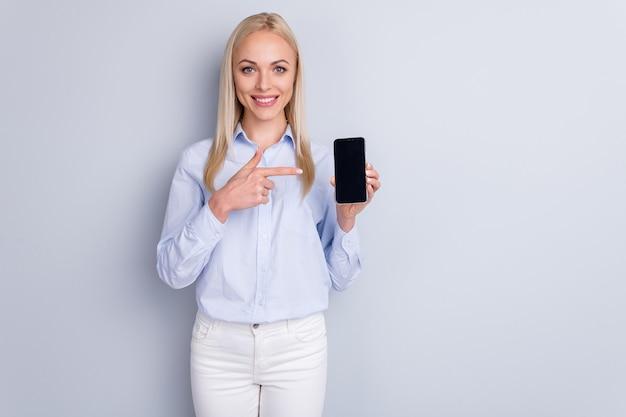 긍정적 인 쾌활한 발기인 소녀의 초상화는 새로운 스마트 폰 장치 포인트 검지 손가락을 잡아