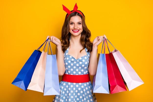 ポジティブで陽気な赤毛の女の子中毒の買い物客の肖像画は旅行を楽しむ多くのバッグを購入する明るい色の背景の上に分離された赤いヘッドバンド青いポルカドットヴィンテージスタイルの服を着る
