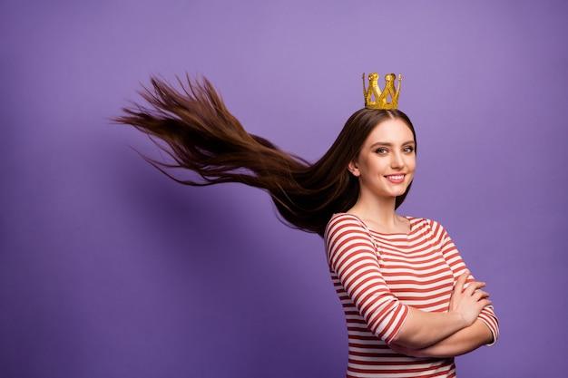 Портрет позитивной жизнерадостной умной старшеклассницы, скрестившей руки, гордящейся своей выпускной вечеринкой, выигравшей стрижку с золотой короной, бросок мухи, белый свитер, изолированный на фиолетовой стене
