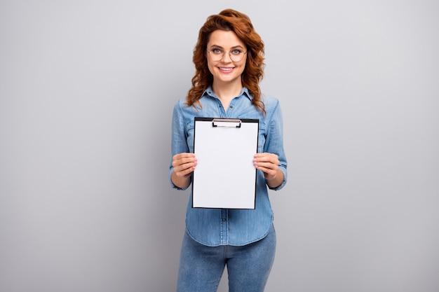 Портрет позитивного жизнерадостного умного успешного работника с буфером обмена показывает белую бумагу для подписи партнерства, одетую в красивую одежду, изолированную на стене серого цвета