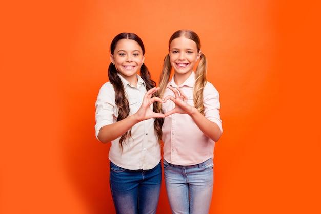 긍정적 인 쾌활한 두 아이 소녀의 초상화는 함께 서서 친절한 사랑의 가족 자매 관계의 심장 손가락 기호 캐주얼 의류 절연 오렌지 색상 배경을 착용합니다