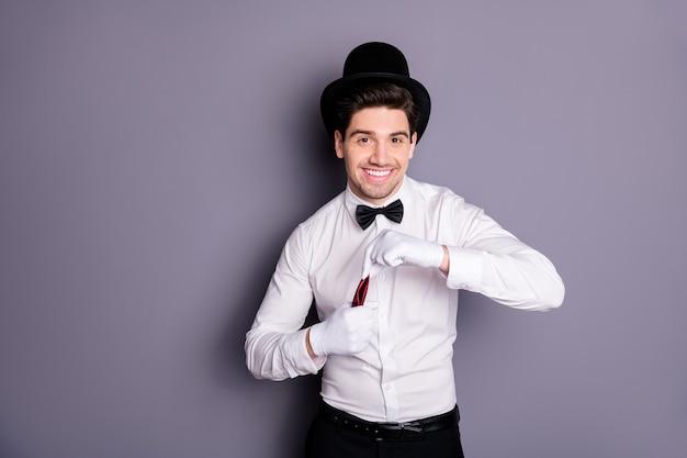 Портрет позитивного жизнерадостного волшебника спрятать красную салфетку в белых перчатках, чтобы заклинания фокусировки носили белую рубашку, черная цилиндрическая шляпа с бантом, изолированная над серой стеной