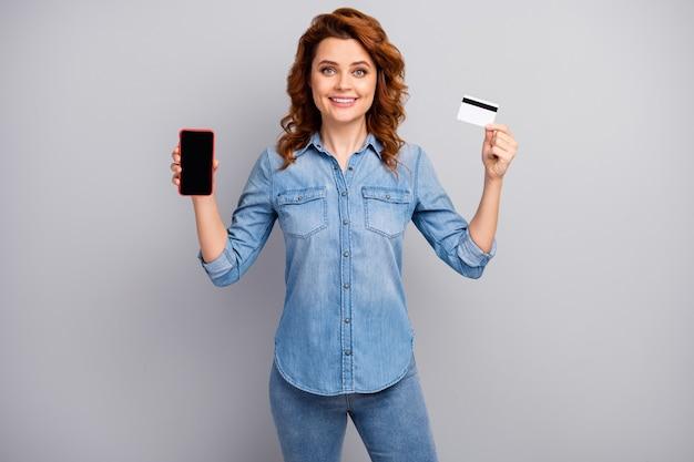 긍정적 인 쾌활한 여자 발기인 보류 스마트 폰의 초상화는 회색 벽 위에 고립 된 온라인 뱅킹 결제 서비스 시스템 착용 스타일 세련된 유행 복장을 권장합니다