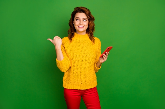 긍정적 인 쾌활한 여자 소셜 네트워크 발기인 포인트 엄지 손가락 직접 방법의 초상화 광고 승진 사용 스마트 폰 착용 스웨터 바지 밝은 광택 컬러 벽 위에 절연