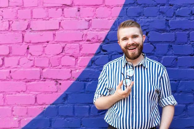 Портрет позитивного веселого молодого стильного человека с усами, бородой и очками в руках, позирующем на фоне сине-фиолетовой кирпичной стены с копией пространства