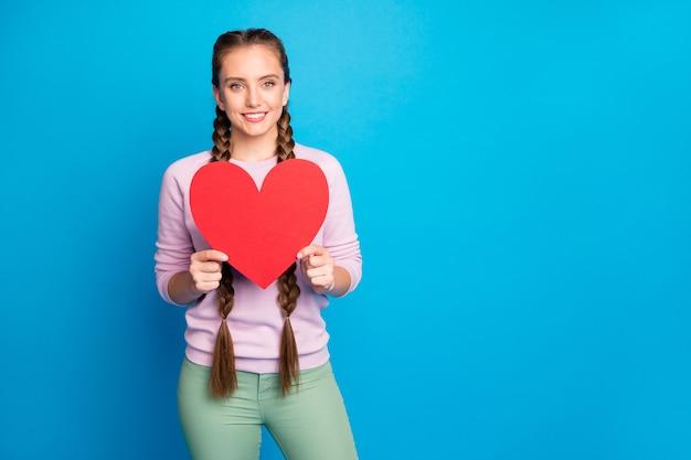 Портрет позитивной жизнерадостной молодой девушки держит красную большую бумажную карточку-сюрприз в виде сердца на 14 февраля.