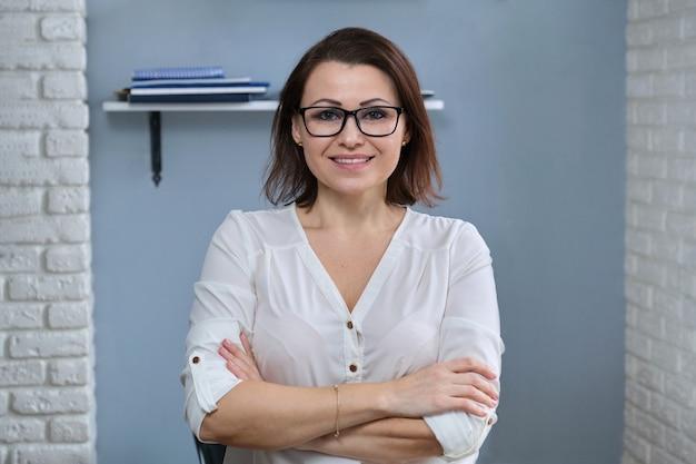 Портрет позитивной уверенной в себе женщины средних лет со скрещенными руками, учителя, консультанта, наставника, тренера, работающего в офисе, улыбающегося, смотрящего в камеру