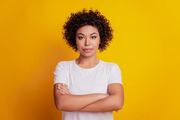 ポジティブな自信を持って若い女の子の肖像画は黄色の背景に手を交差させた