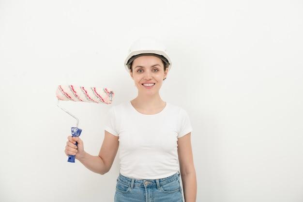 Портрет позитивно уверенной молодой женщины, поправляющей каску и держащей рулон краски у белой стены