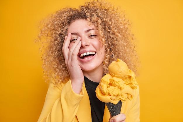 Портрет позитивной кудрявой женщины делает лицо ладонью улыбается, радостно чувствует себя очень рада, наслаждается выходным в компании веселых друзей, ест вкусное высококалорийное мороженое, не заботится о диете