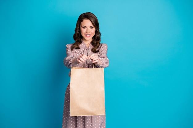 ポジティブかわいいかわいい女の子ホールドパッケージバッグの肖像画は、青い色の背景の上に分離されたショッピングセンターのプレゼントウェア水玉模様の服を与える