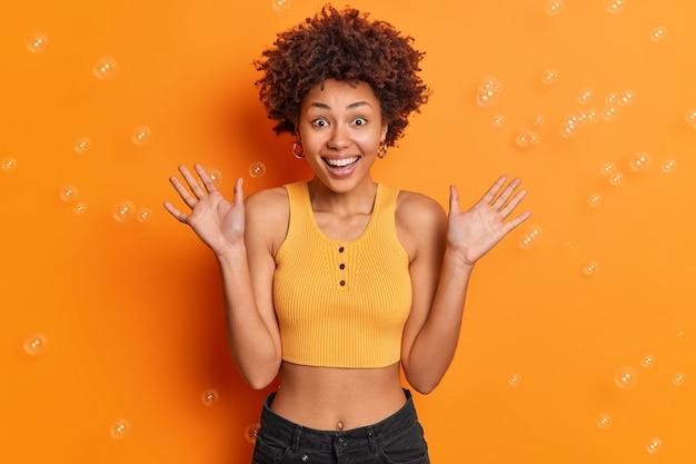 Портрет позитивно-эмоциональной красивой этнической девушки с идеальной фигурой в укороченном топе и брюках, поднимающих ладони, и счастливо смотрится спереди, изолированно над оранжевой стеной, летающими мыльными пузырями
