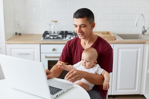 赤ちゃんの男の子または女の子と膝の上に座って、前向きな表情でラップトップコンピューターを見て、自宅でオンラインで作業している男性の栗色のカジュアルなtシャツを着ている前向きな父親の肖像画。