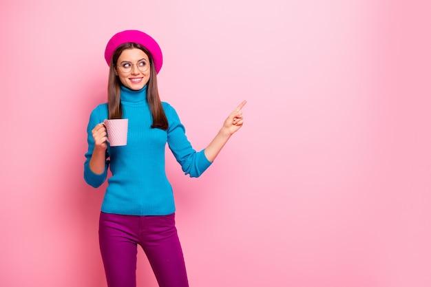 ポジティブなフランス人の女の子の肖像旅行旅行ポイント人差し指コピースペースショーカフェカフェテリア販売促進ホールドカップラテ広告は青いズボンを着用します。