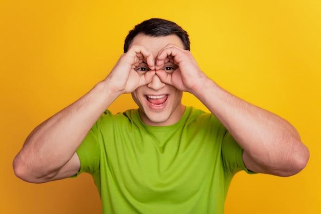 ポジティブなファンキーな男の肖像画は、黄色の背景に浮かんで双眼鏡を手します