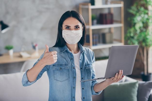 Портрет инфицированной девушки covid19, у больного человека есть карантин, работа на дому, использование ноутбука, показ большого пальца, знак одобрения качества в интернете, ношение респираторной маски в доме